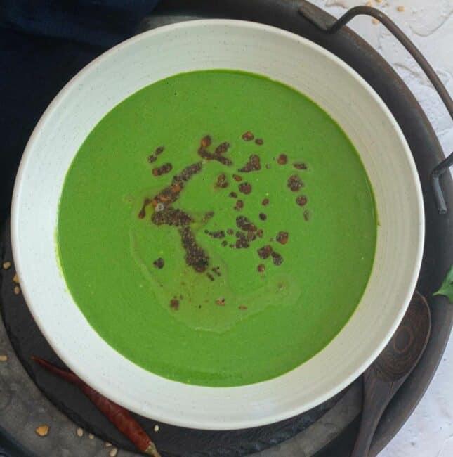 square image of spinach raita in a white bowl