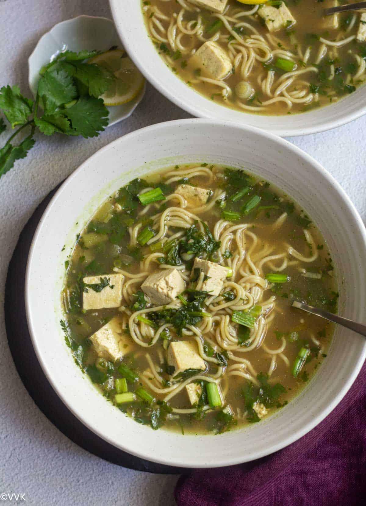 easy one pot lemon cilantro noodle soup served in white bowls