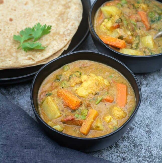 square image of veg kurma served in black bowl with roti on the side