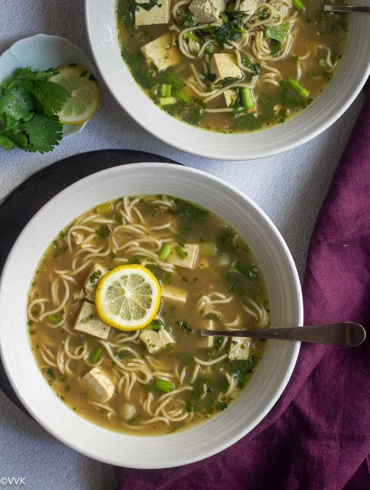 overhead shot of lemon cilantro tofu soup served in white bowls