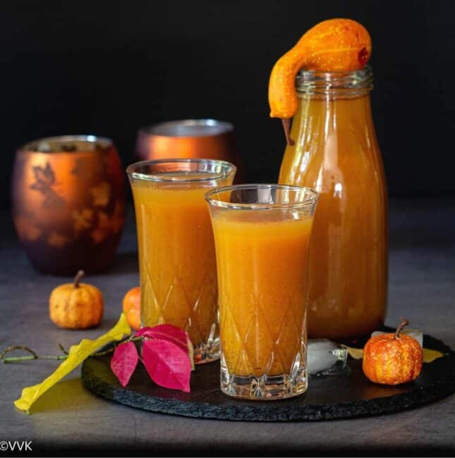 square image of pumpkin juice served in two glasses and in one bottle
