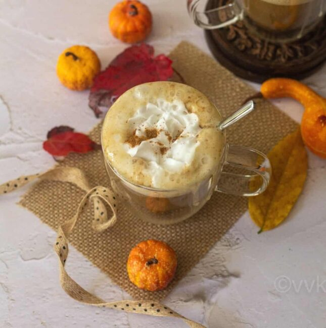 square image of pumpkin spice latte served in a glass placed on a burlap cloth