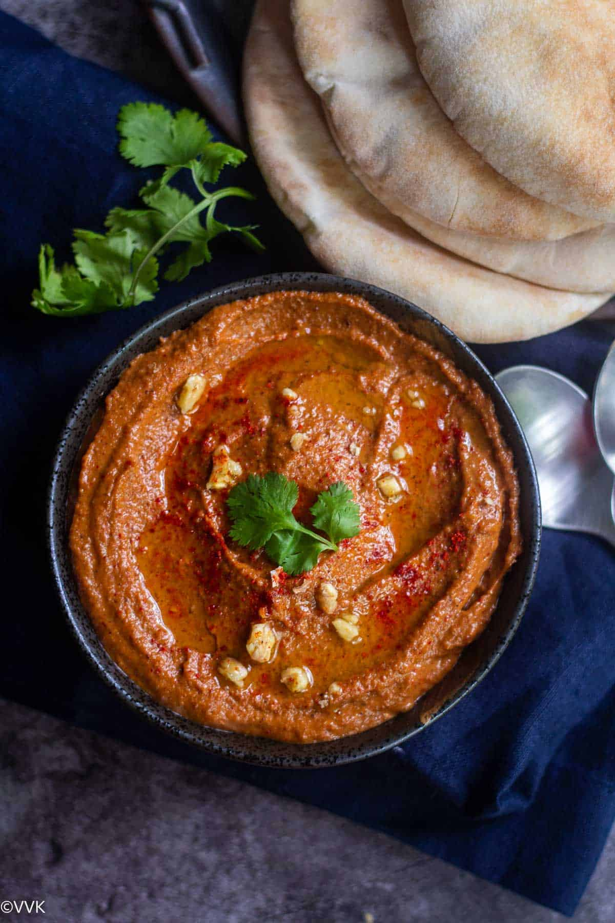 overhead shot of muhammara served in bowl with pita bread on the side placed on a blue towel